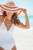 stock photo of suntanning  - Portrait of happy young woman in swimsuit hiding behind beach hat - JPG