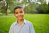 Closeup portrait of smiling mulatto boy in light-blue striped shirt