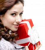 Young woman hands a gift wrapped in red paper, isolated on white, close up