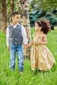 Little girl in beige party frock and boy stand holding hands in park on grassy lawn