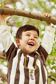 Closeup portrait of laughing little boy who hang on branch grasping at it with hands