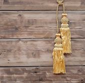 Gold rope with curtain tassel against wooden wall