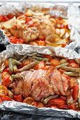 Two cooked chicken dishes in foil