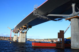 stock photo of flatboat  - bridge construction reaching over water view from beneath - JPG
