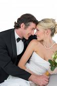 Attractive bride and groom with head to head against white background