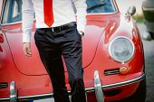 Elegant man with classic car on background