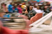 Couple Laughs Riding Scrambler Carnival Ride At Atlanta Fair