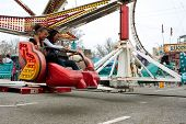 Teens Enjoy Fast Moving Carnival Ride At Fair