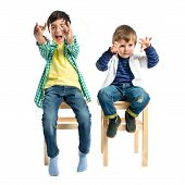 Kids Doing The Horn Sign Over White Background