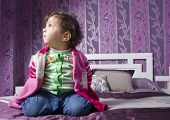 stock photo of 15 year old  - Cute baby one year old sit on bed at home - JPG
