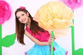 Beautiful young woman in petty skirt holding big flower on decorative background