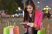 Happy woman shopping and using tablet PC
