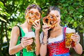 In Beer garden - female friends in Tracht, and Dirndl drinking a fresh beer and eating pretzel in Ba