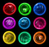 foto of condom  - Colorful condoms isolated on black background in studio - JPG
