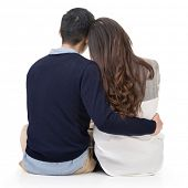 Young couple sitting on ground and hugging, full length portrait isolated on white background.