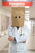 Doctor covering head with paper bag inside hospital