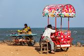 PONDICHERRY, INDIA - FEBRUARY 2, 2013: Unidentified Indian street vendors of ice cream and snacks wi