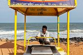 PONDICHERRY, INDIA - FEBRUARY 2, 2013: Unidentified Indian street ice cream vendor with cart on beac