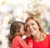 family, child and happiness concept - smiling mother and daughter whispering gossip