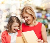 family, child, holiday and party concept - smiling mother and daughter opening gift box