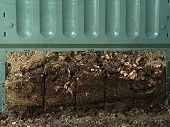 Closeup of green plastic compost bin with lower part removed to show advanced soil decomposition pro