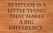 Attitude is a little thing that makes a big difference - quote by Winston Churchill on wooden red oak background