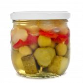 a jar with spanish banderillas, skewers with different pickles, such as olives, garlic, cucumbers, onion and red pepper