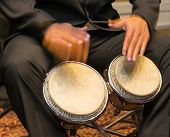 stock photo of caribbean  - Salsa musician playing the bongos a percussion instrument traditional for the Caribbean and Latin American music - JPG
