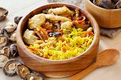 picture of curry chicken  - chicken curry with pilau rice and shiitake in wooden bowl mushrooms on kitchen table - JPG