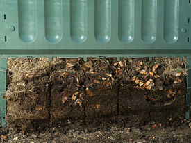 foto of decomposition  - Closeup of green plastic compost bin with lower part removed to show advanced soil decomposition process - JPG