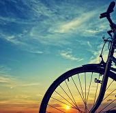 image of color wheel  - Beautiful close up scene of bicycle at sunset sun on blue sky with vintage colors silhouette of bike forward to sun wonderful rural of Mekong Delta Vietnam countryside - JPG
