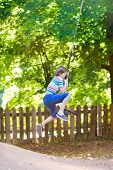 Funny Little Boy Enjoying A Swing Ride On A Playground On A Beautiful Sunny Summer Day