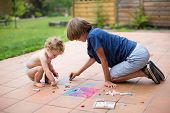 Brother And His Baby Sister Playing Together In The Backyard Painting On The Ground With Colorful Ch