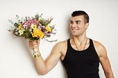 Young man poses with bouquet