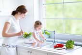 Young Mother And Her Adorable Toddler Daughter Cooking Salad Together In A Sunny White Kitchen