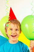 Little smiling boy in holiday hat with festive balls and streamer