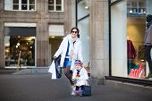 Young Beautiful Mother And Her Adorable Toddler Girl Having Fun Together At A Winter Sale Shopping