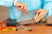 Serviceman parses electronic hardware for repair in service workshop
