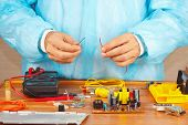 Hands repairman servicing electronic devices in service workshop