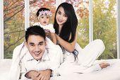Hispanic Family On Bedroom In Autumn