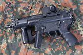 stock photo of mp5  - modern 9 mm submachine gun on camouflaged background - JPG