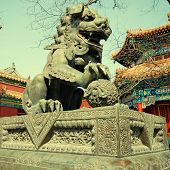 stock photo of lamas  - Ancient bronze lion and red chinese paviliones in famous Lama Temple  - JPG