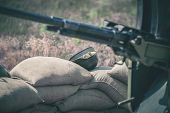 stock photo of mg  - Old vintage machine gun standing with sandbags - JPG
