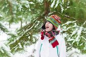 Funny Little Boy Screaming Of Joy Playing Snow Ball Fight In Snowy Winter Park Under Christmas Tree