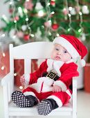 picture of christmas baby  - Funny Newborn Baby Boy In A Santa Outfit Sitting Under A Decorated Christmas Tree - JPG
