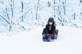 stock photo of sleigh ride  - Little Boy Enjoying A Sleigh Ride In A Snowy Forest - JPG