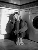 stock photo of lonely  - lonely depressed and sick woman sitting alone on kitchen floor in stress depression and sadness feeling miserable in barefoot looking desperate in black and white vertical composition - JPG