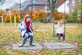Laughing Boy And His Toddler Sister Playing Together On A Swing In Autumn