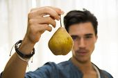 Young Man Holding A Ripe Yellow Pear