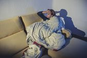 Young Sick Woman Sitting On Couch Wrapped In Duvet And Blanket Feeling Miserable